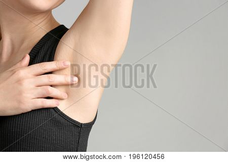 Beautiful young woman on light background. Concept of using deodorant