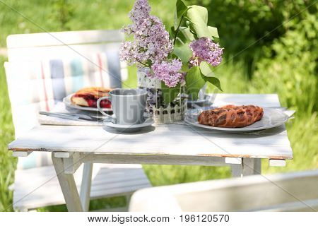 Beautiful table setting for dinner outdoors with lilac flowers