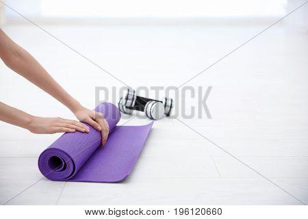 Female hands rolling yoga mat on light background