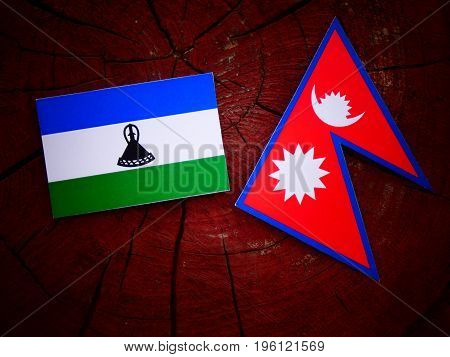 Lesotho Flag With Nepali Flag On A Tree Stump Isolated