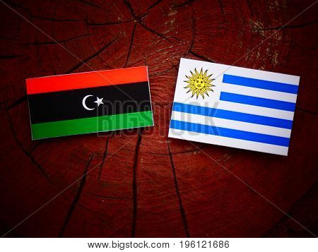 Libyan Flag With Uruguaian Flag On A Tree Stump Isolated