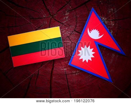 Lithuanian Flag With Nepali Flag On A Tree Stump Isolated