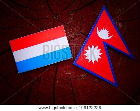 Luxembourg Flag With Nepali Flag On A Tree Stump Isolated