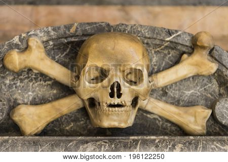 Detail from the decoration of a tomb marble skull with bone