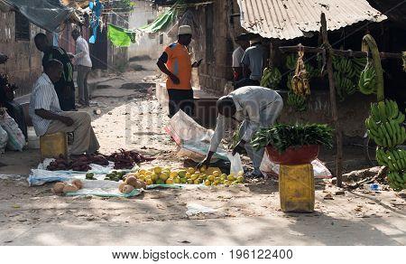 Zanzibar, Tanzania - July 15, 2016: Local farmers of zanzibar, tanzania selling their fruits right on the street, poverty and shacks