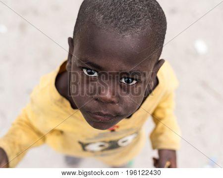 Zanzibar, Tanzania - July 15, 2016: African child of zanzibar, tanzania with his head shaved looking upward, big serious eyes