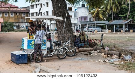 Zanzibar, Tanzania - July 15, 2016: Young muslim boy living on zanzibar selling sparkling water, street trade and ruined buildings
