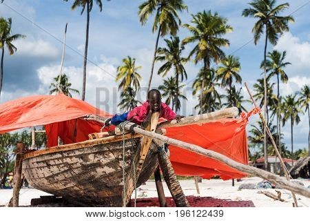 Zanzibar, Tanzania - July 15, 2016: Black child of zanzibar, tanzania sitting on his rustic wooden fishing boat and orange tent