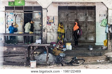 Zanzibar, Tanzania - July 15, 2016: Women in burkas of zanzibar, tanzania coming to a local store to get bananas, trade