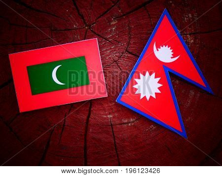 Maldives Flag With Nepali Flag On A Tree Stump Isolated