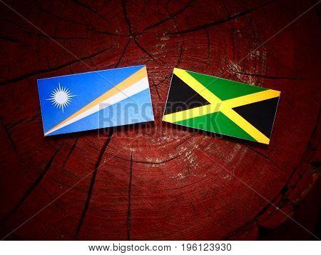 Marshall Islands Flag With Jamaican Flag On A Tree Stump Isolated