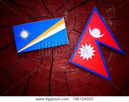 Marshall Islands Flag With Nepali Flag On A Tree Stump Isolated