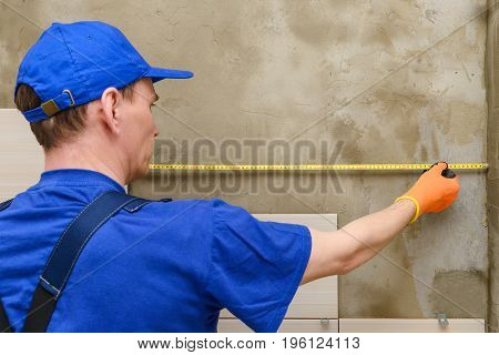 The master in the working overalls measures the distance for laying the tiles on the wall
