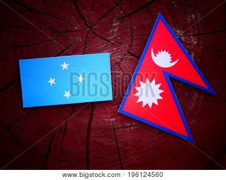 Micronesian Flag With Nepali Flag On A Tree Stump Isolated