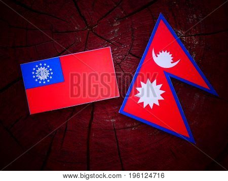 Myanmar Flag With Nepali Flag On A Tree Stump Isolated