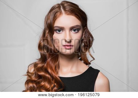 Portrait of charming curly woman posing in the studio
