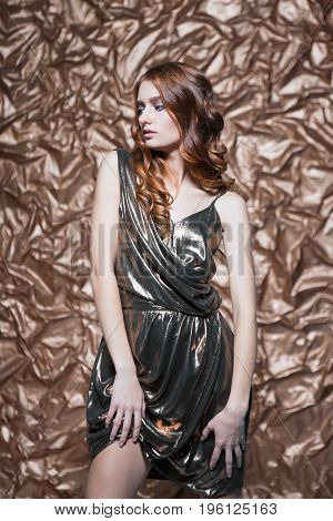 Portrait of sexy thoughtful woman wearing glossy dress posing in the studio
