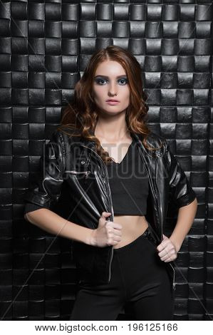 Portrait of fashionable young woman wearing black clothes posing in the studio