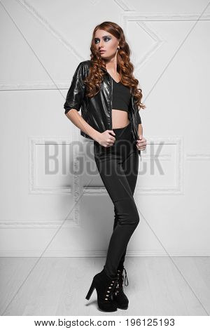Thoughtful curly woman dressed in black leggings and leather jacket posing near the wall