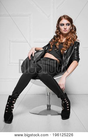 Thoughtful curly lady wearing black fashionable clothes sitting in a chair