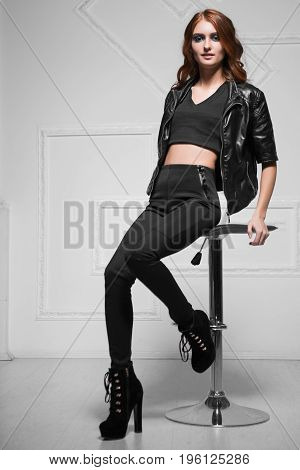Leggy curly woman wearing black fashionable clothes posing in a chair