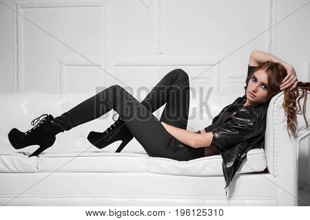 Stunning young model lying on the sofa in black fashionable clothes
