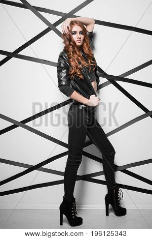 Playful red-haired woman wearing fashionable clothes posing in the studio