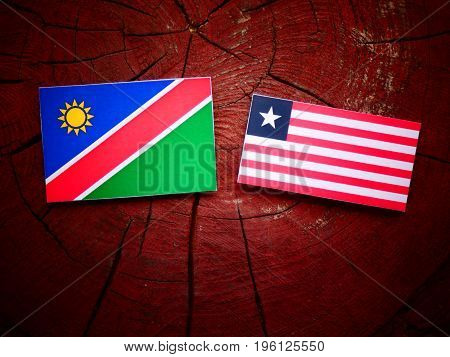 Namibian Flag With Liberian Flag On A Tree Stump Isolated