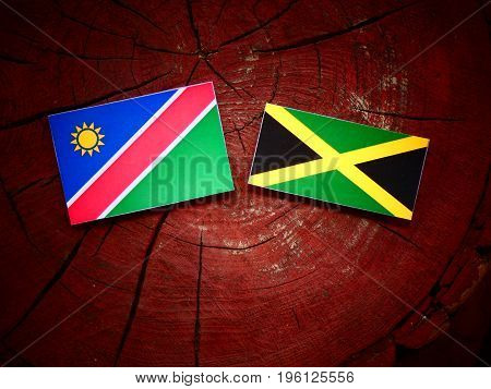 Namibian Flag With Jamaican Flag On A Tree Stump Isolated