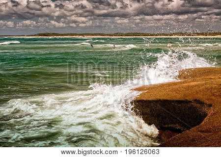 The Pacific waves splash on the rocks of a beach in Caloundra Queensland Australia. The surfers are ready for a morning ride.