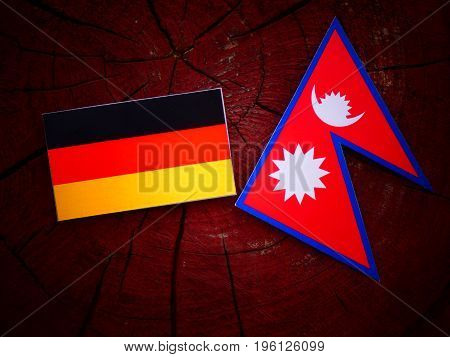 German Flag With Nepali Flag On A Tree Stump Isolated