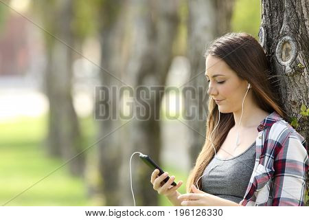 Relaxed girl listening on line music and watching media content leaning on a tree in a park