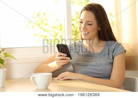 Single girl chatting on a mobile phone sitting in a table at home