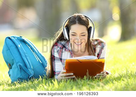 Front view portrait of a student reading notes and listening an audio tutorial on line lying on the grass in a park