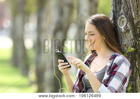 Beautiful teen girl listening and choosing music in a smart phone leaning on a tree in a park