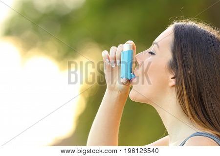 Side view of a woman using an asthma inhaler outdoors with a green background