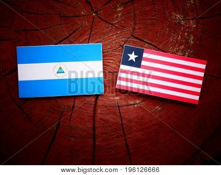 Nicaraguan Flag With Liberian Flag On A Tree Stump Isolated
