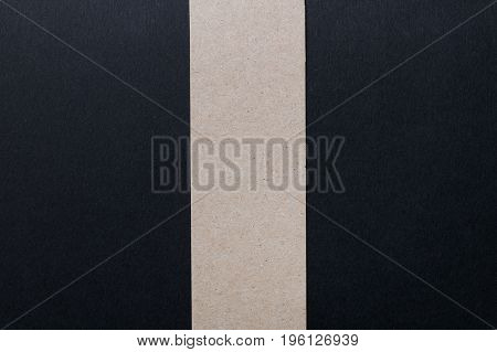 A black sheet of paper divided in half by a vertical stripe of kraft paper. Abstract composition.