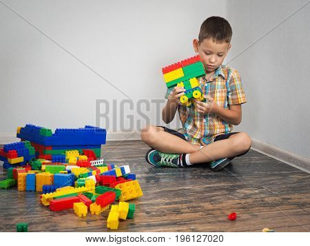 boy plays in the construction. Colorful toy designer a lot of details