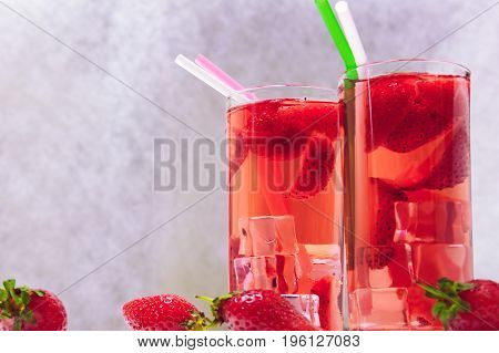Detox with strawberries and ice on a white wooden background