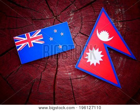 New Zealand Flag With Nepali Flag On A Tree Stump Isolated