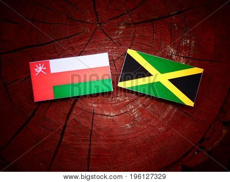Omani Flag With Jamaican Flag On A Tree Stump Isolated