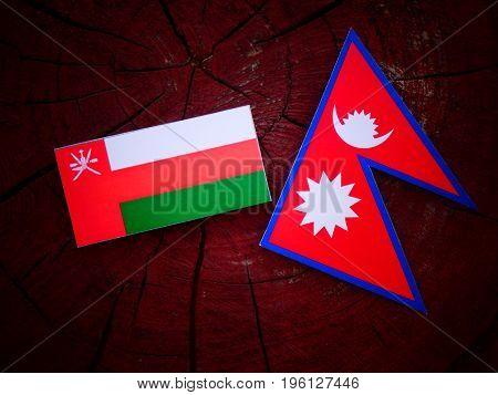 Omani Flag With Nepali Flag On A Tree Stump Isolated