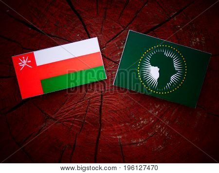 Omani Flag With African Union Flag On A Tree Stump Isolated