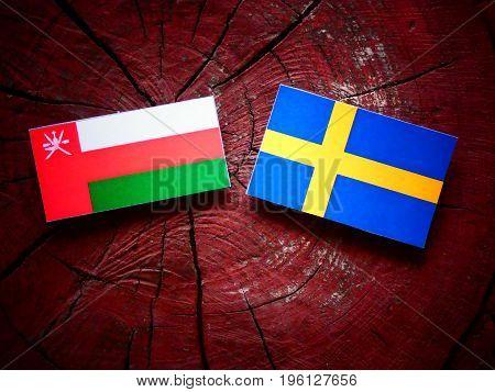 Omani Flag With Swedish Flag On A Tree Stump Isolated