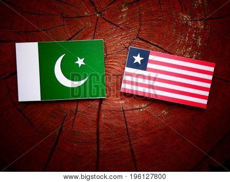 Pakistani Flag With Liberian Flag On A Tree Stump Isolated