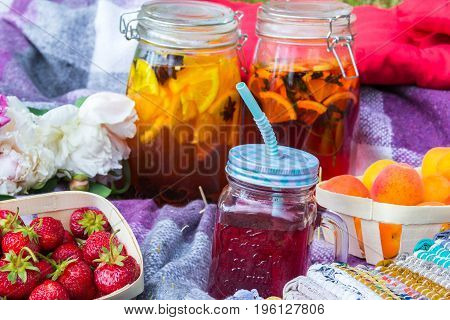 Picnic in the outdoor with strawberry apricots and different cold beverages