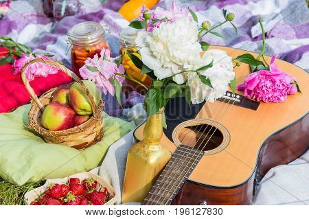 Picnic in the outdoor with guitar apples strawberry beverages pillows and peonies in the vase
