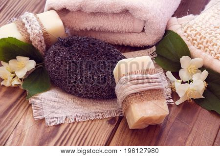 Two pieces of dry soap with a jasmine towel pumice and a bast on a wooden background