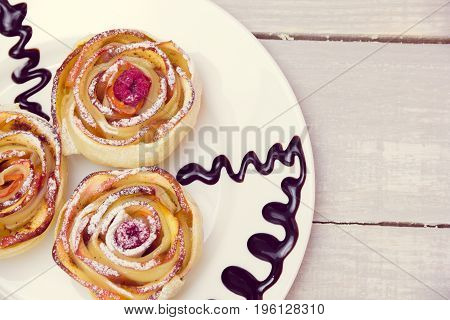 three apple muffins with raspberries in the center drizzled with chocolate sauce leaving a zigzag trail on a white plate on a wooden grey background